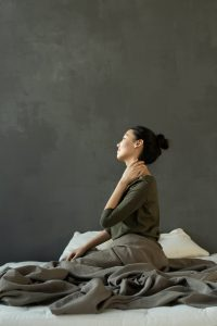 A woman sitting up in bed with her hand on her neck